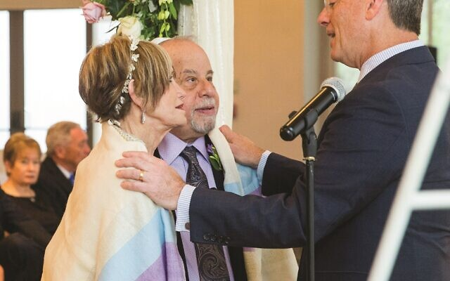Rabbi Ron Segal of Temple Sinai officiates the ceremony and blesses the newly married couple. (Credit: Life on Film Photography)