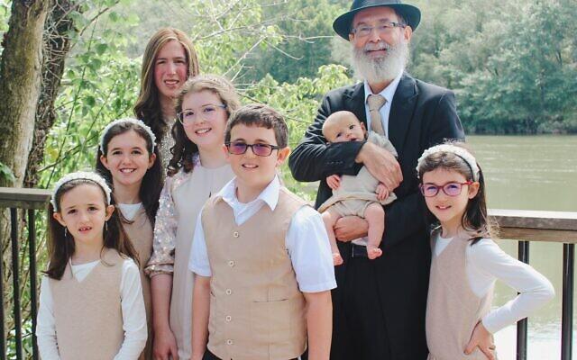 Photos by Malka Griffin// The Antopolskys stop for a photo: (l to r) Chana, Shayna, Esther, Yaffa, Avraham, David (holding Chaya Mushka), Eliana.