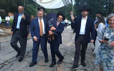 Photos by Allen H. Lipis // Shimon Kaminetzky and his son, Sam, march with the 50-year-old Torah