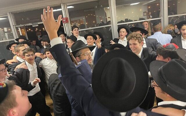 Photos by Allen H. Lipis // As the march approached Yeshiva Ohr Yisrael, a group of students came out to welcome the Torah to its new home.