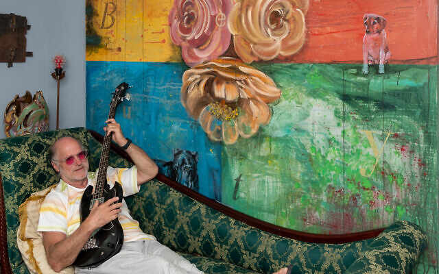 """Jeffrey strums his guitar in front of Linda's painting """"Beauty."""""""