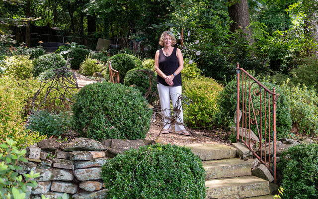 Linda in the couple's expansive backyard, surrounded by a collection of metal sculptures.