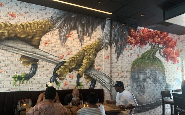 The painted wall mural is somewhere between an eagle's talons, a bulbous floral pink tree, and a spoon.