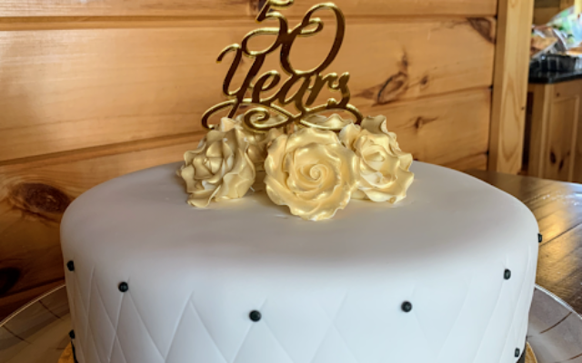 A  beautiful cake was the centerpiece for the evening, along with gold embellishments and personalized toasts.