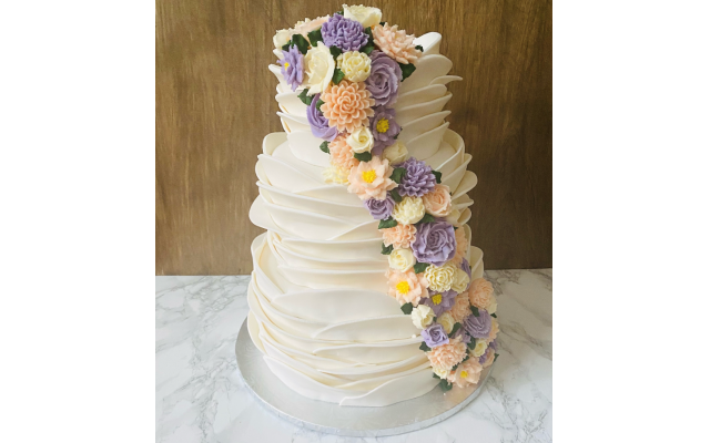 Flavored wedding cakes covered in fondant and  hand-piped buttercream flowers.