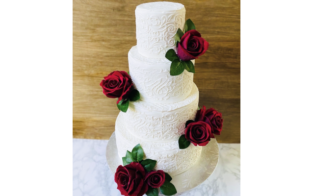 Wedding cakes covered in fondant and flowers.