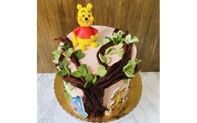 Winnie-the-Pooh vanilla cake covered in buttercream and decorated with handmade fondant accents for a baby shower.