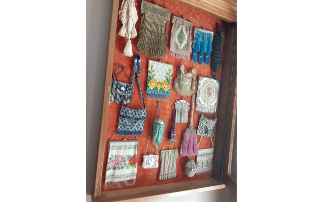 Display case of 21 vintage purses.