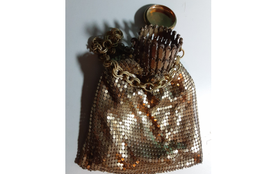 Gold metal mesh bag with accordion opening and removable cap.