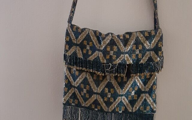 This geometrically-designed iridescent purse has beautifully beaded fringe and strap