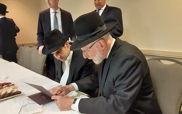 hotos by Joel Alpert/ Market Power // Checking the ketubah before the ceremony. Cameron (center) pays close attention to details.