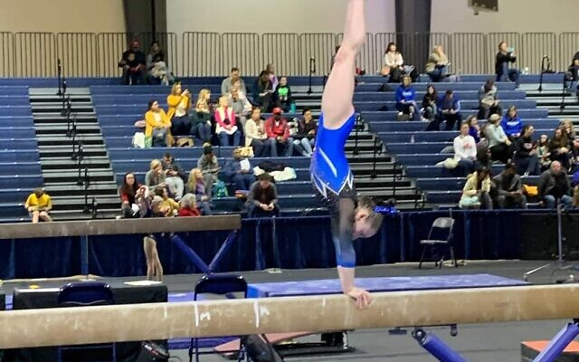 Mia demonstrates a Level 5 handstand on beam.