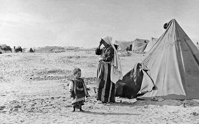 In this 1948 photo from the UNRWA archive, Palestinian refugees stand outside their tent in Khan Younis, Gaza Strip. (photo credit: AP/UNRWA Photo Archives)