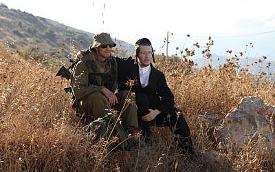 Illustrative: Soldiers of the IDF's ultra-Orthodox Netzah Yehuda Battalion sit in a field at the Peles Military Base, in the Northern Jordan Valley. (Yaakov Naumi/Flash90)