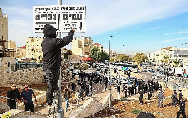 "Police stand guard as Beit Shemesh municipal workers take down ""modesty"" signs in the city on December 11, 2017. (Yaakov Lederman/Flash90)"