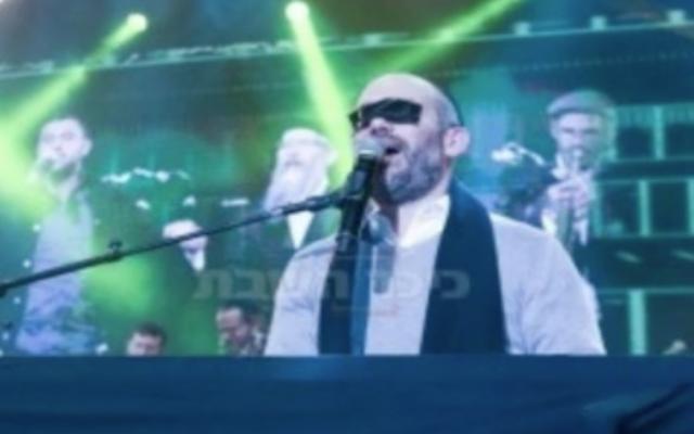 Yonatan Razel, with masking tape over his eyes, at a Jerusalem concert for women on December 3, 2017 (Hadashot news screenshot)