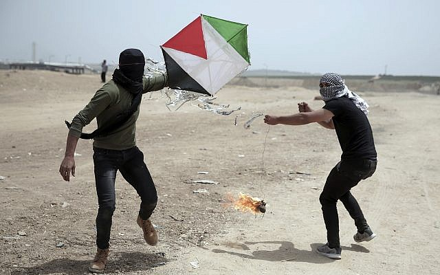 Palestinian protesters fly a kite with a burning rag dangling from its tail to during a protest at the Gaza Strip's border with Israel, April 20, 2018. (AP Photo/ Khalil Hamra)