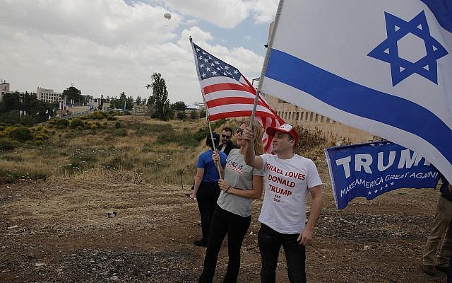Israelis hold American and Israeli flags with the new US Embassy in the background in Jerusalem, May 14, 2018. (AP Photo/Sebastian Scheiner)
