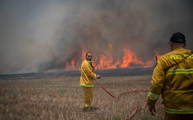 File: Israeli firefighters battle a blaze in a field in southern Israel caused by kites flown by Palestinians from the Gaza Strip on June 5, 2018. (Yonatan Sindel/Flash90)