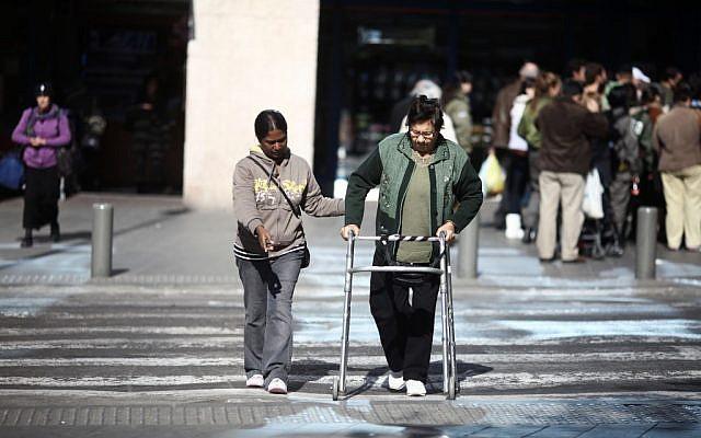 Illustrative: A carer helping an elderly Israeli to cross the street in Tel Aviv. (Kobi Gideon/Flash90)