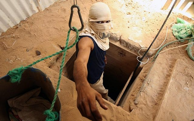 A masked man emerges from a tunnel linking the Gaza Strip to Egypt (photo credit: Abed Rahim Khatib /Flash90)
