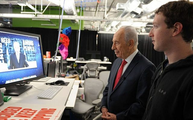 Former President Shimon Peres works on his Facebook page with Mark Zuckerberg, founder of Facebook, looking on (photo credit: Moshe Milner/GPO/Flash90)