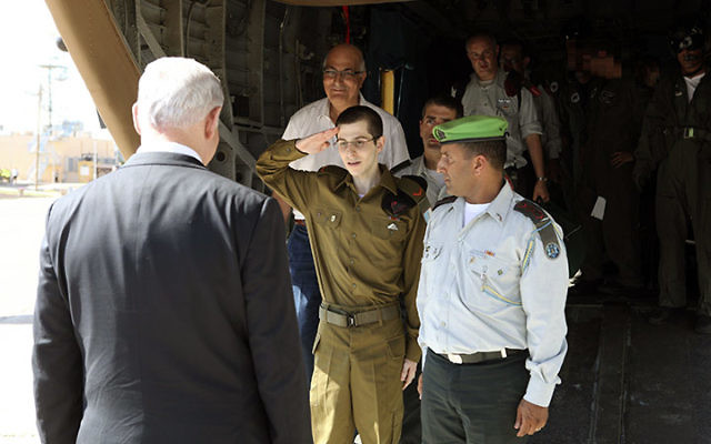 Corporal Gilad Shalit salutes Prime Minister Netanyahu, shortly after his release from captivity last October (Associated Press).