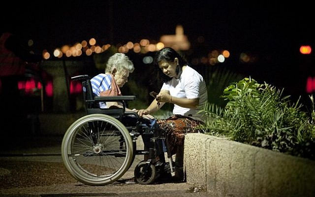 Illustrative: A Filipina caretaker with an elderly Israeli woman on the Tel Aviv boardwalk (Moshe Shai/Flash90)