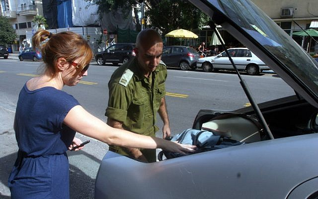 An Israeli reserves officer prepares to leave his Tel Aviv home on Thursday (Photo credit: Roni Schutzer/ Flash 90)