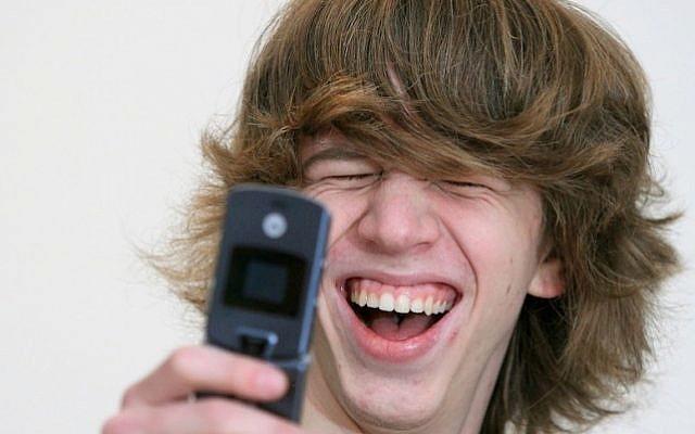 Israeli teen uses his cellphone (Photo credit: Moshe Shai/Flash90)