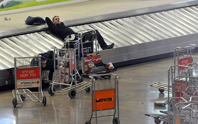 A traveler rests on the luggage belt at Ben Gurion International Airport during a strike in 2010 (photo credit: Yossi Zeliger/Flash90)