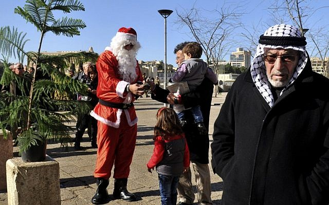 A man dressed as Santa Claus distributes Christmas trees to Christians outside Jaffa Gate in the Old City of Jerusalem on Sunday, Dec. 23, 2012. (photo credit: Mahmoud Ilean/AP)