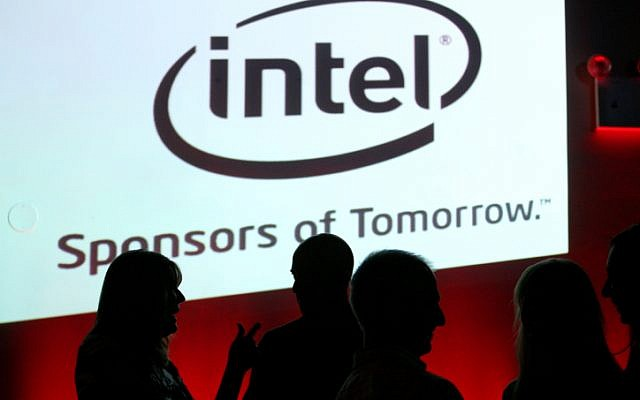 Israelis stand in front of a sign for the hi-tech company Intel. (photo credit: Moshe Shai/Flash90)