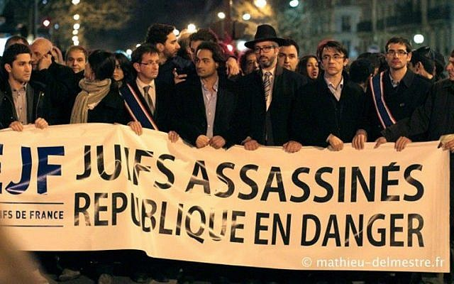 """Members of the Union of French Jewish Students demonstrate in Paris in 2013 with a sign that reads, """"Jews murdered, republic endangered."""" (Courtesy of UEJF via JTA)"""