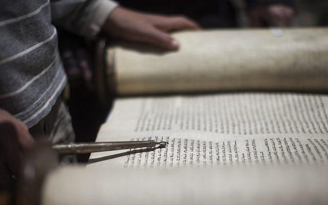 Illustrative photo of a young man reading from a Torah scroll (Yonatan Sindel/Flash90)