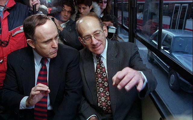 New York mayor Rudy Giuliani, left, gestures as he rides Jerusalem's bus No.18 with Jerusalem's mayor Ehud Olmert, on a visit in 1996 (AP/Brian Hendler)