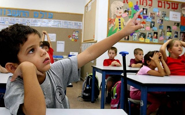 A first grader raises his hand in a classroom in Nitzan, southern Israel. (Edi Israel/Flash90/File)