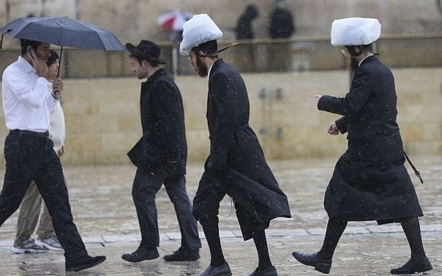 Ultra-Orthodox Jewish men wearing covering on their hats to protect them from the rain at the Western Wall, in Jerusalem's Old City, on a rainy, winter day.  (photo credit: Nati Shohat / Flash90)