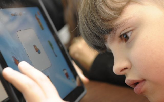 A child at Beit Issie Shapiro developing fine motor skills and hand eye coordination with an iPad