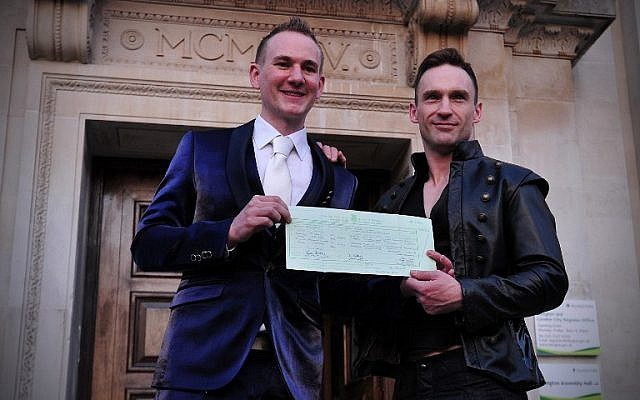 A couple poses for photographs after their same-sex wedding in north London on March 29, 2014 (photo creit: AFP/Carl Court)