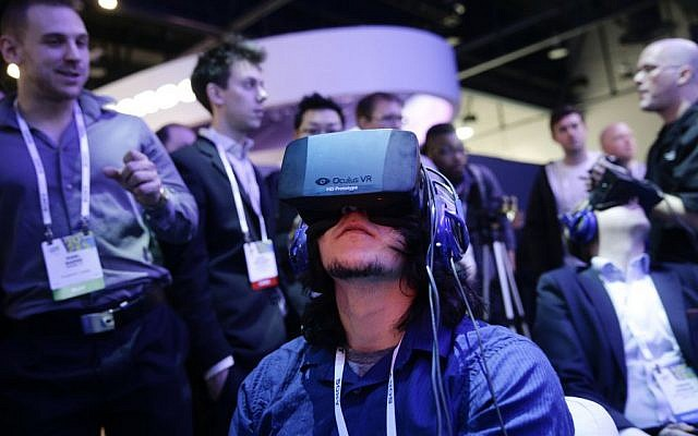 Attendees play a video game wearing Oculus Rift virtual-reality headsets at the Intel booth at the International Consumer Electronics Show (CES), in Las Vegas, 2014. (photo credit: AP/Jae C. Hong, File)