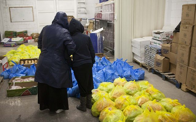 A mother and her daughter stand inside a food distribution center for the needy, in Jerusalem on March 7, 2013 (photo credit: Yonatan Sindel/Flash90)