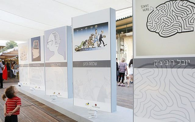 """A young boy looks at an exhibition depicting thematic brain caricatures at the """"First Station"""" in Jerusalem (Photo credit: Miriam Alster/FLASH90)"""