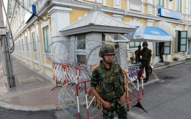 Thai soldiers stand guard at a roadblock outside the Defense Ministry building (background) after Thailand's army chief announced that the armed forces were seizing power, in Bangkok on May 22, 2014 (photo credit: AFP/Christophe Archambault)