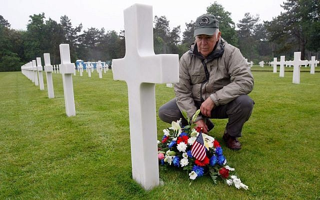 Paul Clifford, 70, from Boston MA, USA, places flowers on the grave of Walter J. Gunther Jr, the uncle of his best friend, in the Normandy American Cemetery and Memorial, in Colleville sur Mer, France, Wednesday June 4, 2014. (photo credit: AP Photo/Claude Paris)