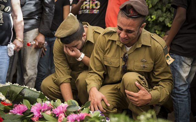 Fellow soldiers seen mourning over the fresh grave of Golani soldier, Moshe Malko, at the Har Herzl Military Cemetery in Jerusalem, on July 21, 2014. Staff Sgt. Moshe Malko, 20, from Jerusalem, was killed July 20 before dawn during combat in the Gaza Strip. (photo credit: Hadas Parush/Flash90)