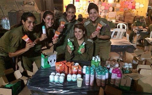 IDF soldiers hold Garnier care packages.  (StandWithUs)