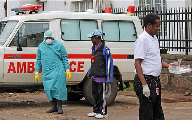 Health workers outside Connaught Hospital after the arrival of a patient with symptoms of the Ebola virus in the city of Freetown, Sierra Leone,  August 4, 2014. (photo credit: AP/Youssouf Bah)