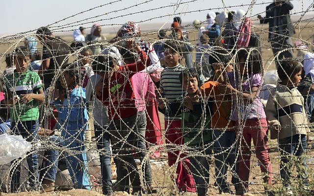 Several hundred Syrian refugees wait to cross into Turkey at the border in Suruc, Turkey, on Sunday, September 21, 2014. (photo credit: AP Photo/Burhan Ozbilici)