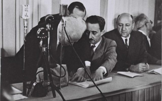 Ben Gurion (left) signing Israel's Declaration of Independence, held by Moshe Sharet, with Eliezer Kaplan looking on.